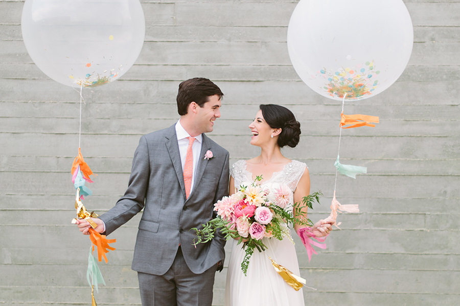 Bride and groom fun wedding day portrait with giant balloons and streamers at Trinity River Audubon Cetner in Dallas