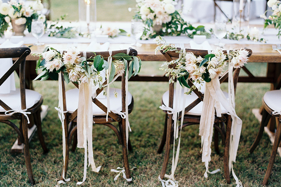 Crosback wedding chairs with floral garland and streamers