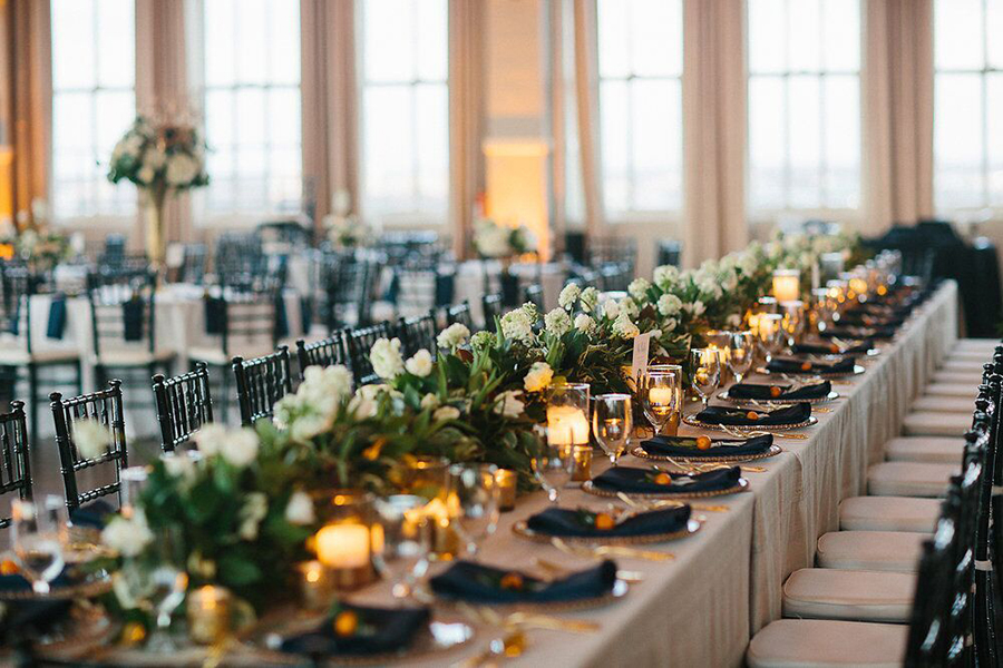 Long wedding reception head table with green and white floral garland, candles and placesetting with kumquats
